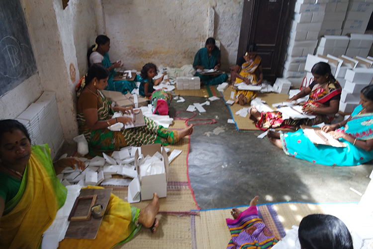 Women packing hygiene bags for hotels.