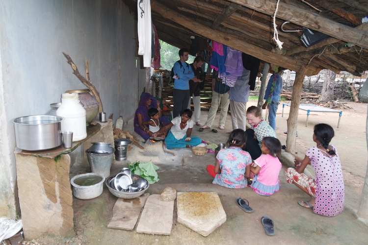 STEM MBA student Rachel Ramey learns to make bread over the small wood-fueled stove used for cooking in the tribal village we visited in the Panna Forest.